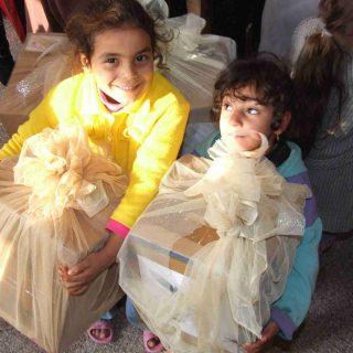 الاطفال الفلسطينين فى معبر رفح يحملون الهدايا
