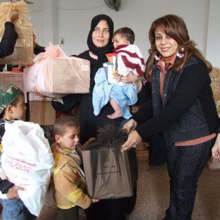 السيدة حنان نصر وهي تهدي طفل من اطفال فلسطين هدية عيد الاضحى