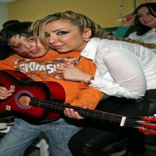 نادين تحتضن الطفل الذي ستتكفل بعلاجه لمرضه بمرض نادر جدا